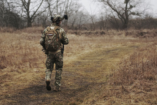 Soldier walking on brown grass. Joining the military can allow you to move out with no money.