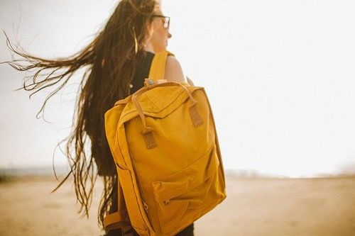 Girl carrying a yellow backpack, can't afford to move out.
